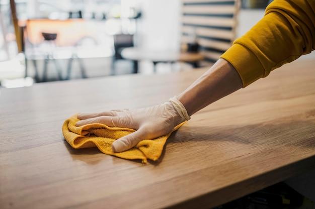 Widok z boku stołu do czyszczenia baristy podczas noszenia rękawicy lateksowej