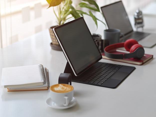 Widok z boku stołu roboczego wygrywającego przestrzeń do pracy z tabletem cyfrowym, laptopem, materiałami eksploatacyjnymi i doniczką