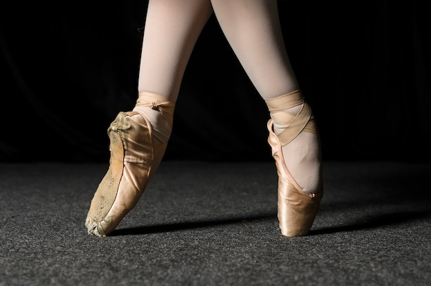 Widok z boku stóp baleriny w pointe butach i rajstopach