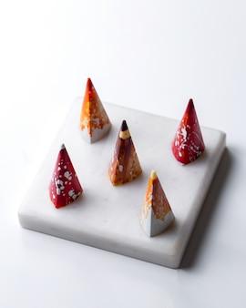 Widok z boku stożkowy wielobarwny w białą cukierek czekoladowy na białym stojaku