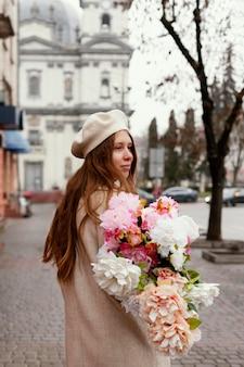 Widok z boku stylowej kobiety na zewnątrz gospodarstwa bukiet kwiatów na wiosnę