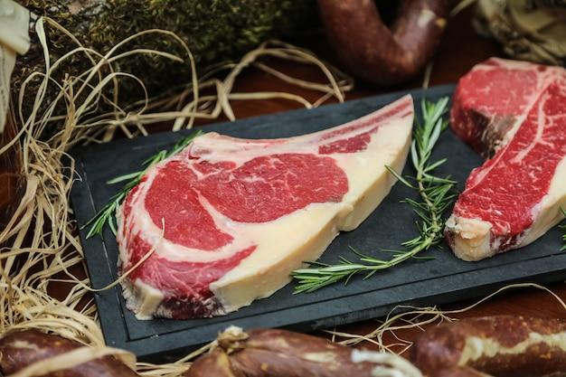 Widok z boku surowe mięso na stek z rozmarynem na stojaku