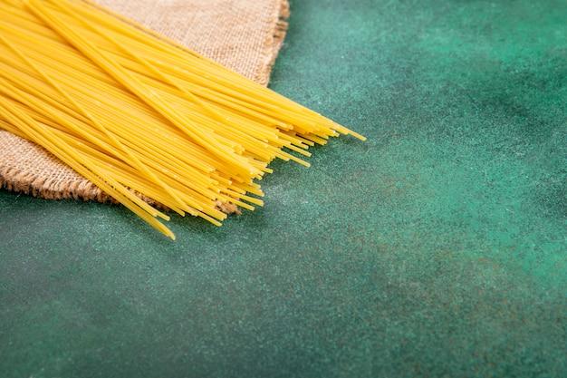 Widok z boku surowego spaghetti na zielonej powierzchni