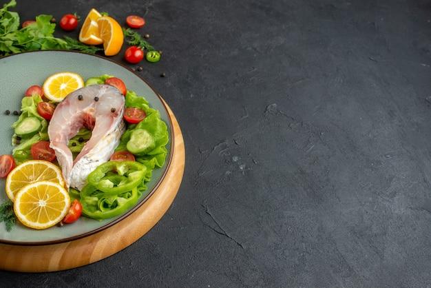 Widok z boku surowej ryby i świeżych posiekanych warzyw plasterki cytryny przyprawy na szarym talerzu na okrągłej desce na czarnej postarzanej powierzchni