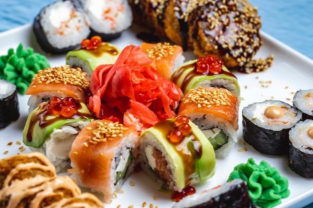 Widok z boku sushi zestaw philadelphia z roladą smoka łososia z imbirem z awokado i wasabi na talerzu