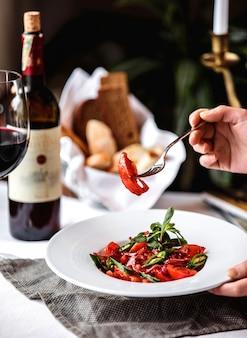 Widok z boku świeżej sałatki z pomidorami zielony pieprz chili czerwony cebulowy sos granatowy w białej misce