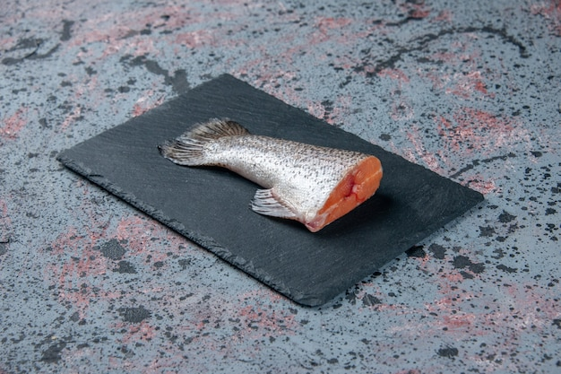 Widok z boku świeżej surowej ryby na ciemnej tacy na niebiesko-czarnym stole mix kolorów z wolną przestrzenią