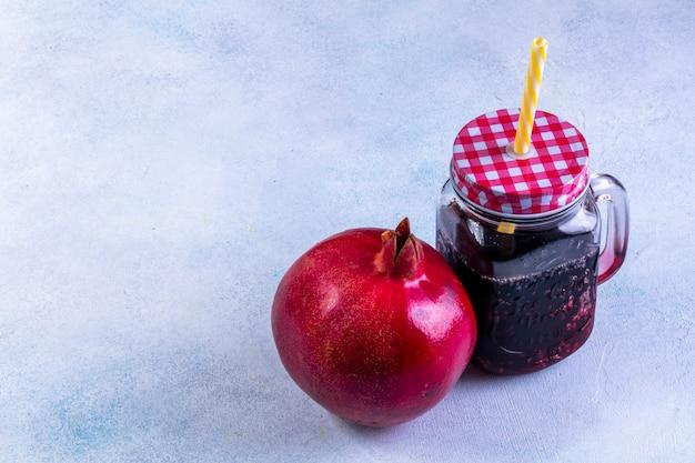 Widok z boku świeży sok z granatów w kubku z pokrywką i granat na niebieskim stole