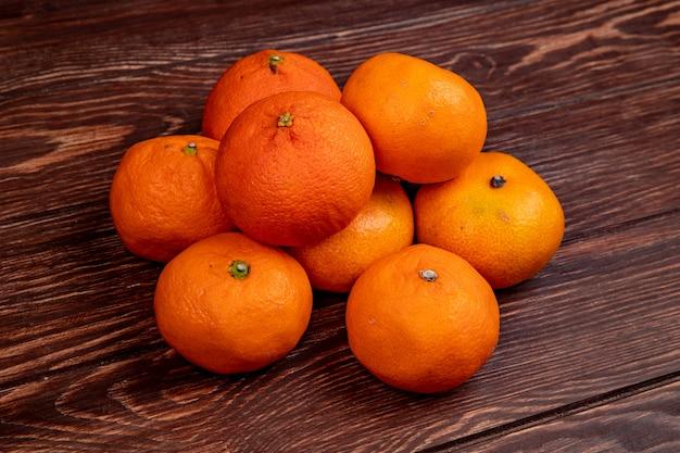 Widok z boku świeżych dojrzałych mandarynek izolowanych na rustykalnym drewnie