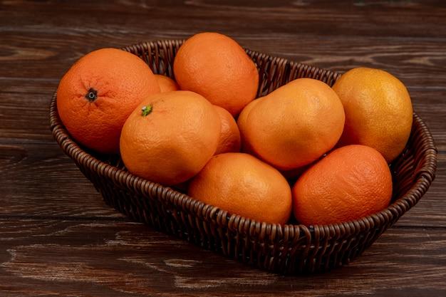 Widok z boku świeżych dojrzałych mandarynek w wiklinowym koszu na rustykalne drewno