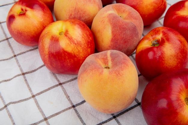 Widok z boku świeżych dojrzałych nektaryn i brzoskwiń na stole w kratę