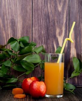 Widok z boku świeżych dojrzałych nektaryn ze szklanką soku brzoskwiniowego na rustykalnym drewnie