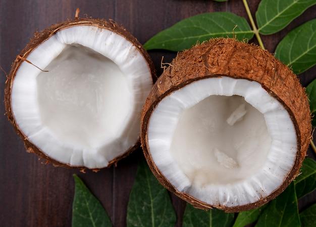 Widok z boku świeżych i brązowych orzechów kokosowych z liściem na powierzchni drewnianych