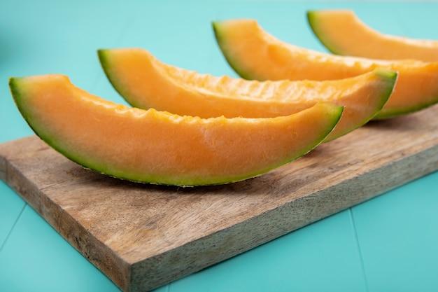 Widok z boku świeżych i pysznych melonów na drewnianej desce kuchennej na niebieskiej powierzchni