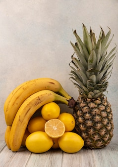 Widok z boku świeżych i smacznych owoców, takich jak banany, cytryny i ananas, odizolowane na szarym drewnianym stole na białym tle