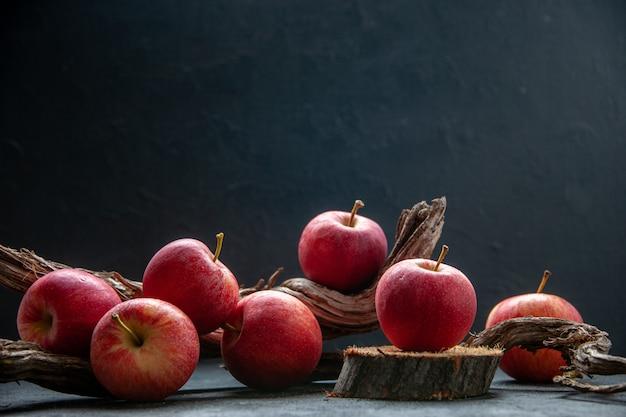 Widok z boku świeżych jabłek na drewnianej desce do krojenia i gałęzi drzewa na świetle na ciemnym tle