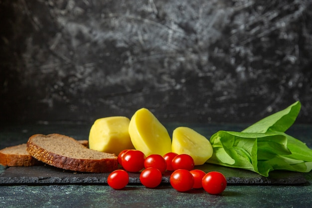 Widok z boku świeżych pokrojonych ziemniaków i kromek chleba dietetycznego pomidory zielony pakiet na drewnianej desce do krojenia na zielonym czarnym tle mix kolorów z wolną przestrzenią