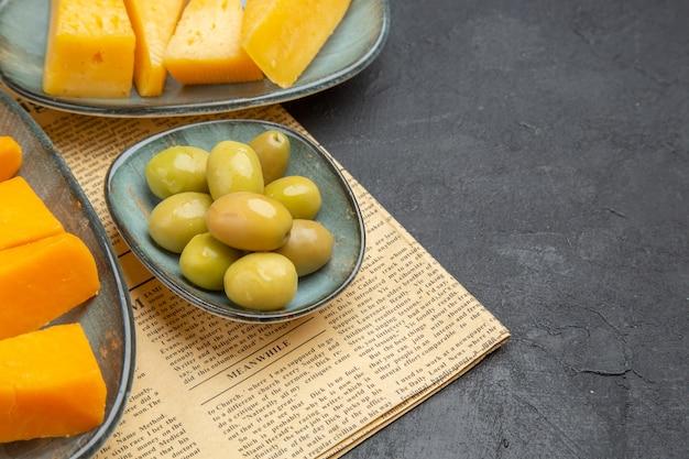 Widok z boku świeżych różnych plasterków sera i zielonych oliwek na starej gazecie na czarnym tle