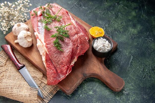 Widok z boku świeżych surowych czerwonych mięs zielony czosnek sól cytrynowa na brązowy drewniany nóż do krojenia na ręcznik w kolorze nude na ciemnym tle