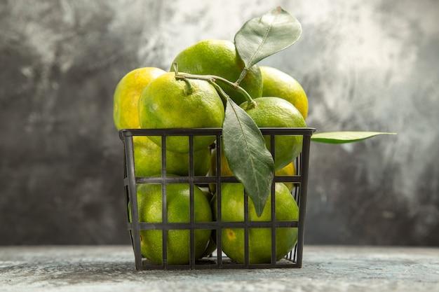 Widok z boku świeżych zielonych mandarynek z liśćmi w koszu na szarym tle