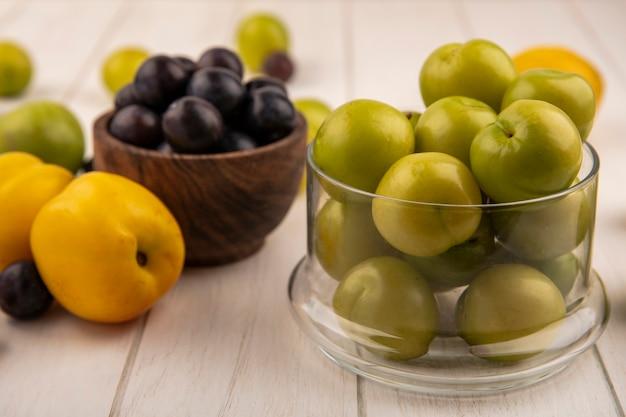 Widok z boku świeżych zielonych śliwek wiśniowych na szklanej misce z tarniny na drewnianej misce z brzoskwiniami na białym tle na białym drewnianym tle
