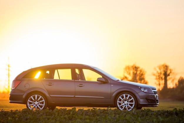 Widok z boku szarego srebrnego pustego samochodu zaparkowanego na wsi na rozmytym wiejskim krajobrazie i jasnym pomarańczowym czystym niebie na tle zachodu słońca. transport, podróże, koncepcja projektowania pojazdów.