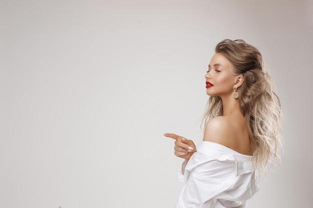 Widok z boku szczęśliwa piękna pani w białej koszuli stojącej i wskazując palcem, aby skopiować miejsce. na białym tle na szarym tle. koncepcja urody i pielęgnacji
