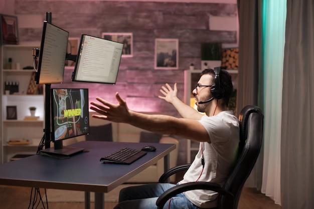 Widok z boku szczęśliwego młodego człowieka o jego zwycięstwie w strzelance online przy użyciu potężnego komputera.