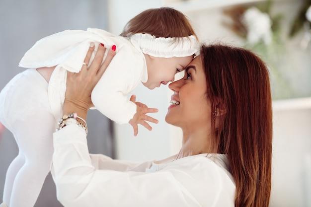 Widok z boku szczęśliwego rodzica i małego dziecka, zabawy podczas gry w domu. koncepcja rodzicielstwa i dzieciństwa