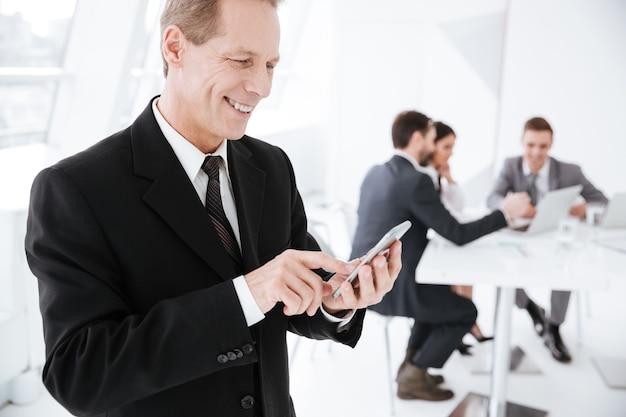 Widok z boku szczęśliwego starszego mężczyzny biznesowego za pomocą telefonu w biurze z kolegami przy stole