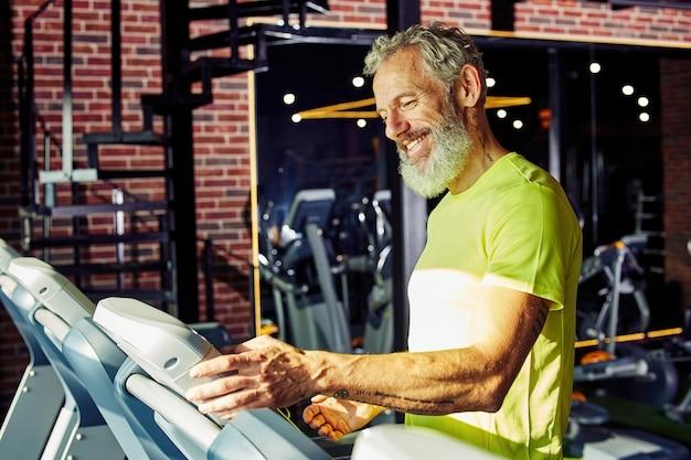 Widok z boku szczęśliwego wysportowanego mężczyzny w średnim wieku w sportowej odzieży dostosowującej prędkość na bieżni, podczas gdy