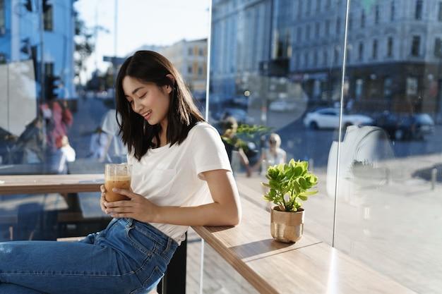 Widok z boku szczęśliwej azjatyckiej kobiety siedzącej samotnie w kawiarni w pobliżu okna, uśmiechając się podczas picia lodowej latte