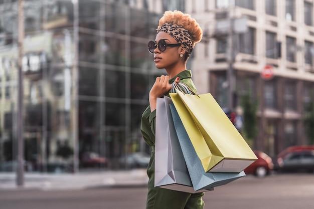 Widok z boku szczęśliwej kobiety afro american z torby na zakupy korzystających z zakupów w mieście