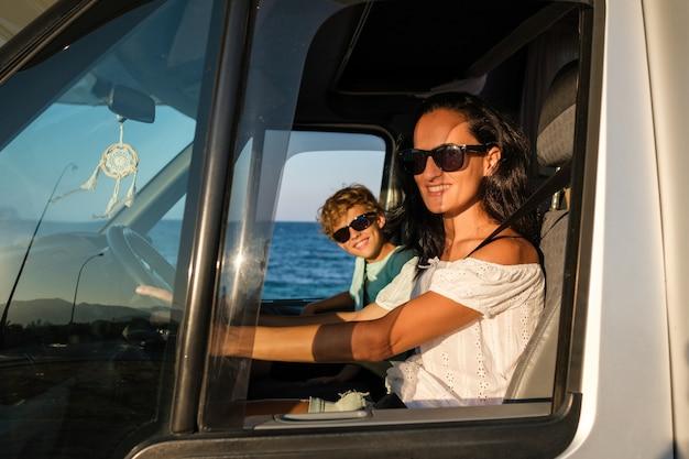 Widok z boku szczęśliwej kobiety i chłopca w okularach przeciwsłonecznych siedzących w samochodzie i patrzących na kamerę przez otwarte okno podczas wspólnej podróży wzdłuż wybrzeża w okresie letnim