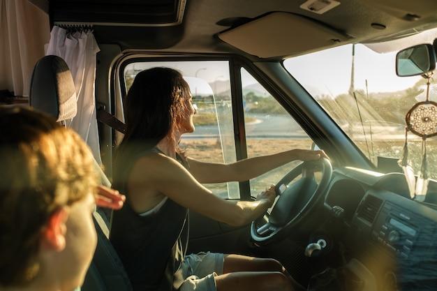 Widok z boku szczęśliwej kobiety prowadzącej samochód kempingowy podczas podróży z synem nad morzem podczas letnich wakacji