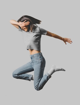Widok z boku szczęśliwej kobiety skaczącej w powietrzu