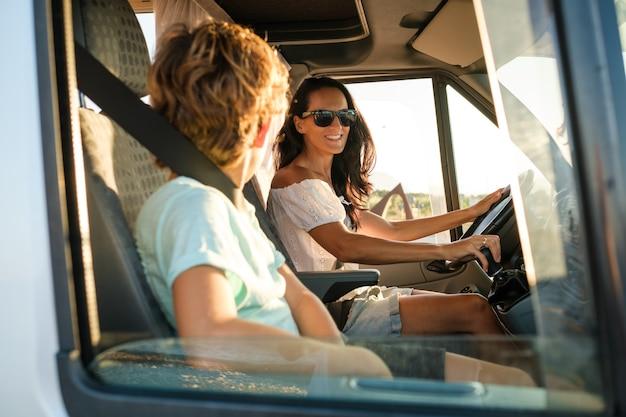Widok z boku szczęśliwej kobiety w okularach przeciwsłonecznych siedzącej na siedzeniu kierowcy w samochodzie kempingowym podczas podróży z synem podczas letnich wakacji