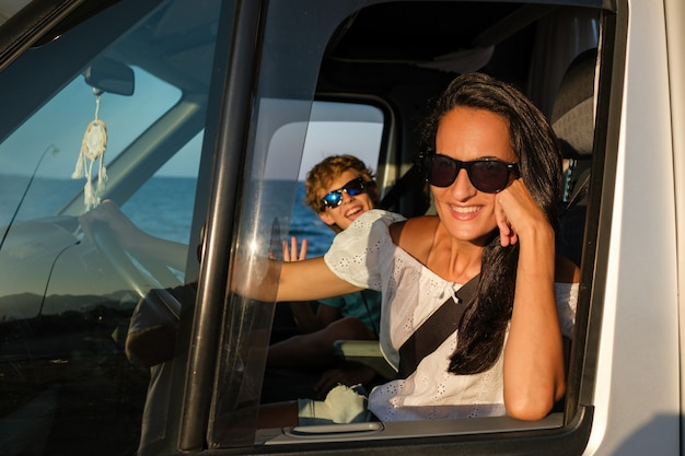 Widok z boku szczęśliwej matki i syna w okularach przeciwsłonecznych siedzących w samochodzie i patrzących w kamerę podczas wspólnej letniej podróży nad morzem