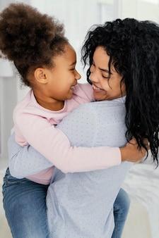 Widok z boku szczęśliwej matki trzymającej córkę buźkę