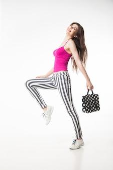 Widok z boku szczęśliwej modelki brunetki w legginsach w paski i różowym z torbą w kropki. izolować.