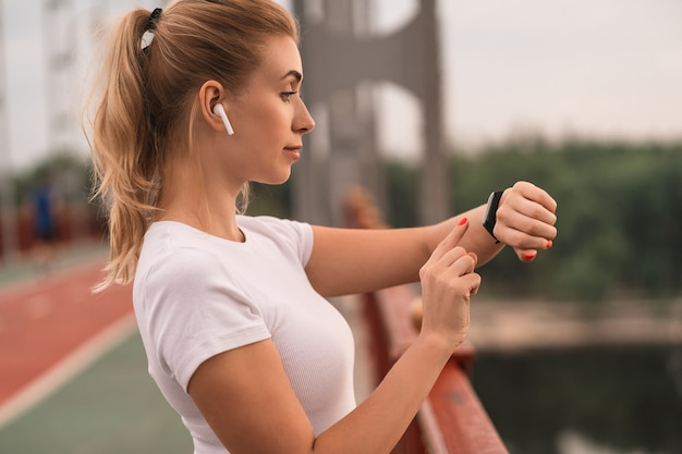 Widok z boku szczęśliwej szczupłej kobiety za pomocą smartwatcha i słuchania muzyki w słuchawkach podczas treningu w mieście