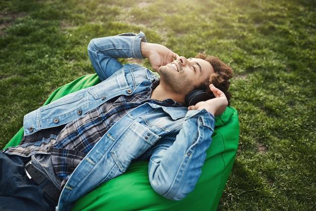 Widok z boku szczęśliwy, atrakcyjny afroamerykanin z fryzurą afro, leżący na fotelu worek fasoli, słuchając muzyki i patrząc w niebo z zrelaksowanym i zadowolonym wyrazem twarzy, spędzając czas w parku