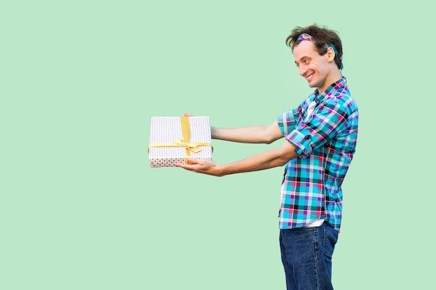 Widok z boku szczęśliwy młody hipster człowieka w białej koszulce i kraciastej koszuli stojącej, dając prezent z żółtą kokardą, uśmiechem toothy. wewnątrz, kopia przestrzeń, izolowane, studio strzał, zielone tło