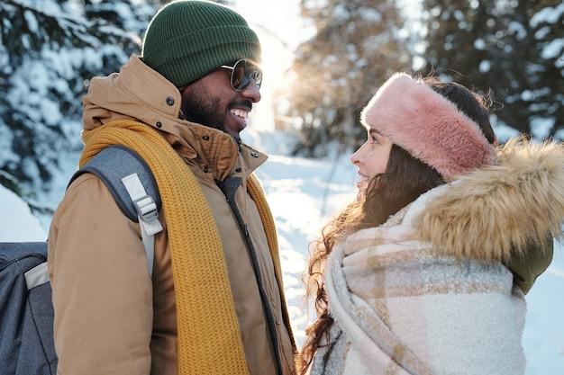 Widok z boku szczęśliwych młodych dat międzykulturowych w odzieży zimowej, patrzących na siebie przed kamerą podczas chłodu w lesie w zimowy weekend
