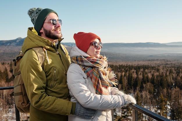 Widok z boku szczęśliwych młodych randek w odzieży zimowej i okularach przeciwsłonecznych, patrzących do przodu na tle błękitnego nieba nad górami pokrytymi śniegiem