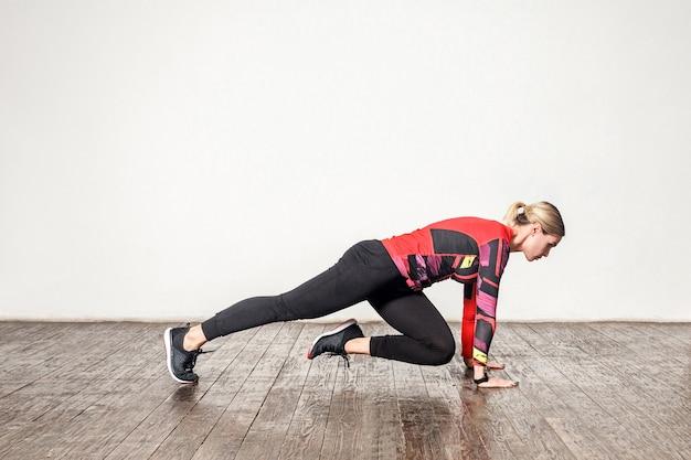 Widok z boku szczupła kobieta lekkoatletycznego w obcisłej odzieży sportowej uprawiania jogi, robienia zgiętej nogi, treningu elastyczności, siły mięśni. opieka zdrowotna, aktywność sportowa i trening w domu. strzał studio w pomieszczeniu