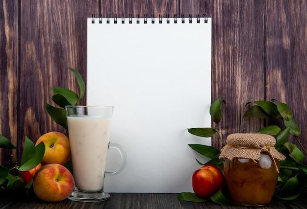 Widok z boku szkicownika z jogurtem w szklanych świeżych dojrzałych brzoskwiniach i miodem w szklanym słoju na rustykalnym drewnianym stole