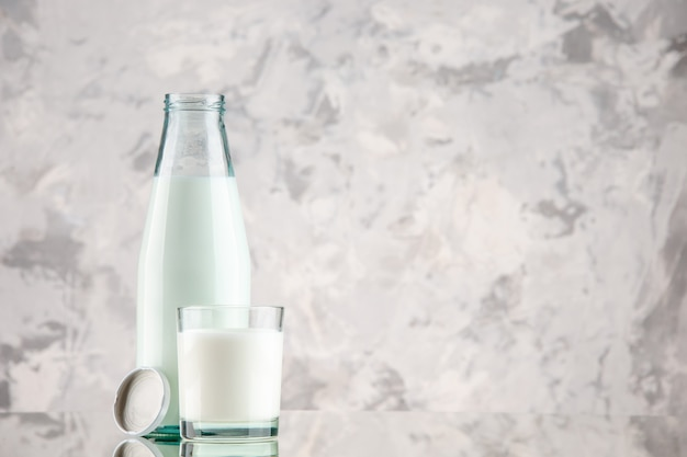 Widok z boku szklanej butelki i kubka wypełnionego nakrętką mleczną po prawej stronie na tle pastelowych kolorów z wolną przestrzenią