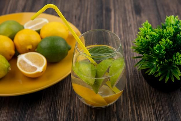 Widok z boku szklanka wody z plasterkami cytryny z wapnem i żółtą słomką na drewnianym tle