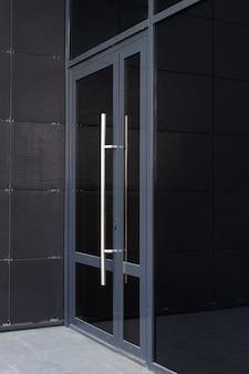 Widok z boku szklanych drzwi - wejście do nowoczesnego budynku biurowego